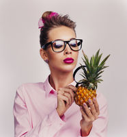 Woman look at pineapple through magnifying glass