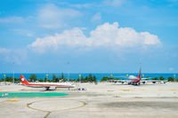Two airplanes in the airport with blue sea on background