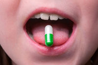 Close up of child puts the pill