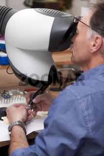 Zahntechniker an einer Lupe