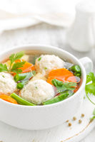 Fresh chicken soup with vegetables and meatballs in a bowl on white background. Top view