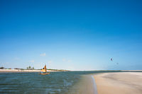 Traditional fishing boat sails along the ocean channel to the tide in Atins, Lencois Maranhenses National Park, Brazil
