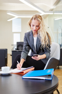 Blonde Geschäftsfrau mit Smartphone