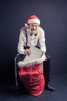 Santa Claus boss pulling laptop from gift bag.