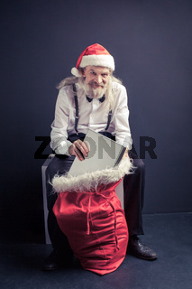 Santa Claus boss pulling laptop from gift bag.