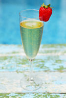 Champagne glass with strawberry on turquiose background