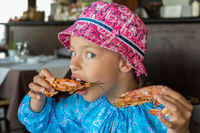 Tourist girl eats large shrimp in cafe on the Sithonia peninsula