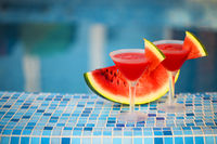 Glasses of watermelon cocktail near the pool
