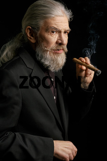 Old man with long grey hair holding cigar.