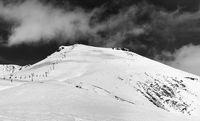 Black and white panorama of snowy ski resort at sun winter day