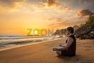 Young sporty fit man doing yoga meditating on tropical beach