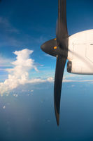 Running turbo airplane propeller in blue sky above the sea