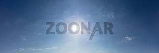 Blauer Himmel mit Sonne als Panorama Hintergrund