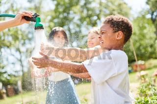 Afrikanischer Junge lässt sich nass spritzen