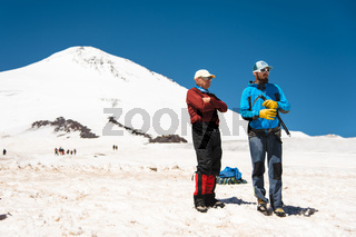 Two climbers talk on training on the right slip on the slope with an ice ax for non-stop braking against the background of a snow-capped high mountain