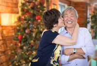 Happy Senior Chinese Couple Kissing In Front of Decorated Christmas Tree.