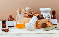 Bottle of essential oil for ayurveda massage with cinnamon stick ,star anise ,bay leaves ginger root and herbal compress ball with selective focus on shabby wooden background .