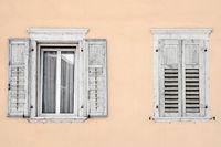 Zwei Fenster mit Fensterläden in einem beigen Haus