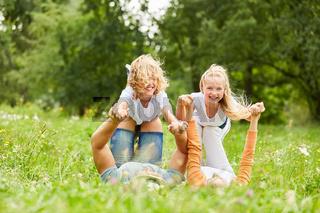 Geschwister Kinder und Eltern spielen zusammen