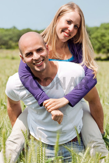 Two young lovers holding each other piggyback