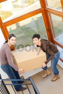 Women carrying cardboard box