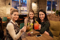 happy friends clinking drinks at restaurant