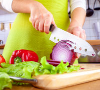 Woman's hands cutting bulb onion