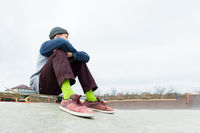 A teenage boy is sitting on a skateboard in the park. The concept of free time pastime for teenagers in the city