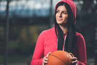 Young female basketball player training outdoors on a local court