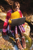 A toned portrait of a a smiling freelancer hipster girl with glasses dressed in a blanket with a laptop kneeling sitting on a rock in a coniferous forest in warm sunlight. The concept of freelancing work at a distance and traveling without interrupting wo