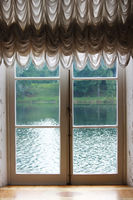 Light from the window with white French curtains and a view of the lake.