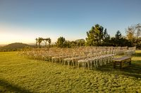 Chairs set up on a lawn for a wedding cerimony with no people yet from the back