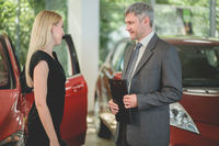 Vehicle dealer selling electric car to young pretty woman.