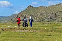Mann mit Motorrad fragt zwei Männer nach dem Weg in der Steppe, Mongolei