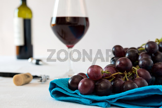 Closeup of a bunch of red grapes and a glass of red wine with a wine bottle