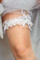 A white lace Garter on the leg of a bride