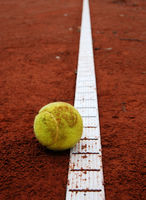Yellow tennis ball on a red court