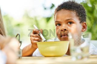 Afrikanischer Junge isst gesundes Müsli