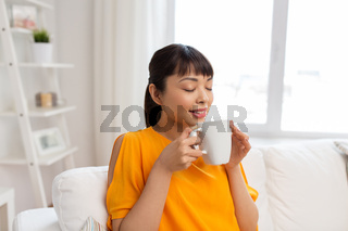 happy asian woman drinking tea or coffee at home