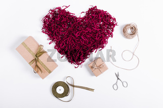 Gifts boxes with ribbons and decorative red heart on a white table