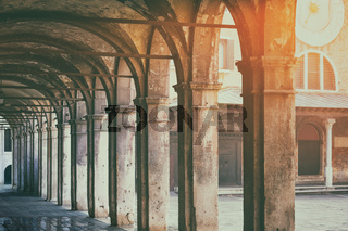 Old arcade passage foot way in sunset light in Venice Italy