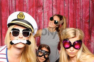 alberne frauen mit sonnenbrillen machen selfie mit fotobox