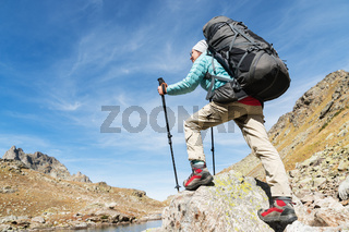 A hiker girl in sunglasses with a backpack and tracking sticks rises to a high rock against the background of rocks and a high mountain lake