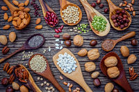 Various legumes and different kinds of nutshells in spoons. Walnuts kernels ,hazelnuts, almond ,brown pinto ,soy beans ,flax seeds ,chia ,chickpea ,red kidney beans and pecan on shabby wooden table.