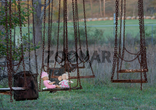 Abandoned childs doll and soft toy on swing