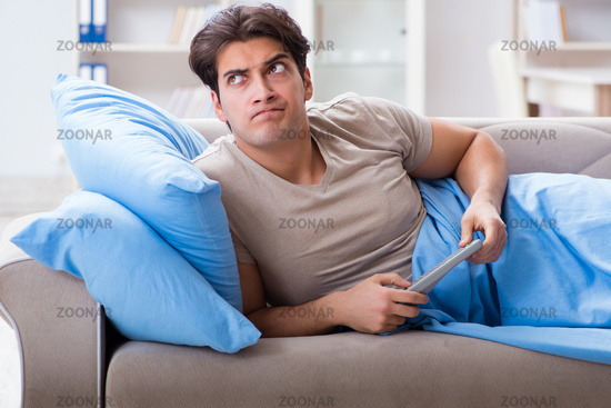 Man watching tv from bed holding remote control unit