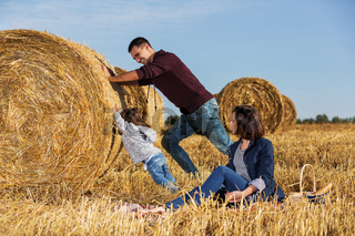 Happy young father and his two year old girl pushing a hay bale in harvested field