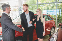 Vehicle dealer passing keys from new car to happy young couple