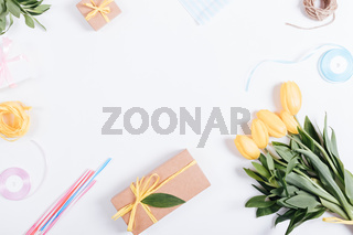 Bouquet of yellow tulips, boxes with gifts, ribbons and rope on a white table, top view
