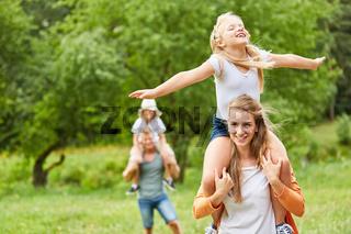 Mädchen hat Spaß auf dem Rücken der Mutter